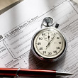 Tax form, red pen and stopwatch — Stock Photo