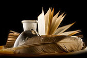 A feather, inkpot, old book and keylock — Stock Photo