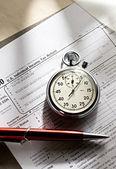 Formulaire d'impôt, stylo rouge et chronomètre — Photo
