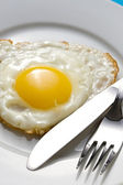 Fried egg on a plate with flatware — Stock Photo