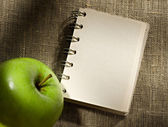 Notepad and apple — Stock Photo
