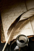 Old book with feather and inkpot — Stock Photo