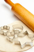 Rolling pin with dough and cookie forms — Stock Photo