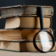 Old books with magnifying glass — Stock Photo