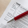 Tax form and a red pen — Stock Photo
