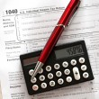 Tax form, red pen and calculator — Stock Photo