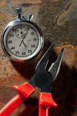 Stopwatch and pliers on the rusty plate — Stock Photo