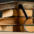 Old books with magnifying glass — Stock Photo #9740343