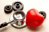 Mechanical ratchets, stethoscope and red heart — Stock Photo
