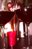 Two glasses of red wine next to the candles — Stock Photo