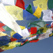 Praying flags floating in the wind on blue sky - Stock Photo