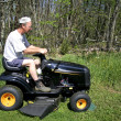 Stock Photo: Msitting on lawnmower