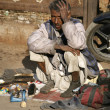 Shoe shiner at Jama Masjid, Delhi, India - Stock Photo