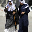 Stock Photo: Old arab men walking and talking in street
