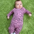 Baby laying on his back on green carpet in pink leopard outfit — Stock Photo