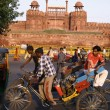 Stock Photo: Rickshaw puller passing by red fort, old delhi, india