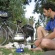 Foto Stock: Camper sitting cooking next bicycle