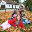 Father and his three children in a park in autumn — Stock Photo