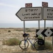 Stock Photo: Bicycle parked against jerusalem and eilat road signs