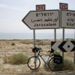 Bicycle parked against the jerusalem and eilat road signs — Stock Photo