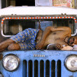 Man dead asleep on jeep, delhi, india - Stock Photo