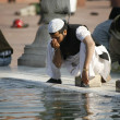 Muslim man performing ablution at Jama Masjid, Delhi, India - Stock Photo