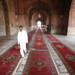 Boy walking on carpet, Jama Masjid, Delhi, India - Foto Stock