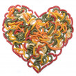 Multi coloured macaroni heart background on isolated white - Stock Photo