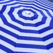 Blue and white striped parasol on beach - Stock Photo