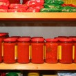 Jars of tomato sauce on the shelf in an organic shop - Stock Photo