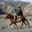 Horse back rider on path, annapurna, nepal - Stock Photo