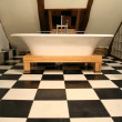 Horizonal view of bathtub on black and white tile floor - Photo
