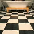 Stock Photo: Vertical view of bathtub on black and white tile floor