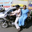 Stock Photo: Couple on motorcycle in traffic, delhi, india