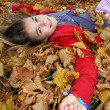 Young girl lying in autumn leaves — Stock Photo
