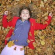 Young girl lying in autumn leaves — Stock Photo #8048910