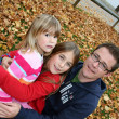 Father with his two daughters sitting in a park in autum leaves — Stock Photo
