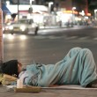 Male homeless sleeping in a street - Stock Photo
