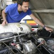 Young man doing mechanical work on car engine - Stock Photo