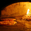 Pizzas baking in an open firewood oven — Stock Photo #8049127