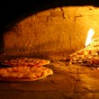 Pizzas baking in an open firewood oven — Stock Photo