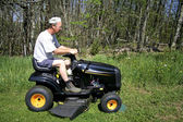 Man sitting on a lawnmower — Stock Photo