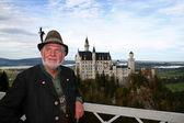 Bavarian man in lederhosen posing infront of neuschwanstein castle — Stock Photo