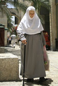 Old nun in jerusalem with her groceries and walking stick — Stock Photo