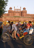 Rickshaw puller passing by red fort, old delhi, india — Stock Photo