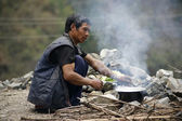 Man preparing food in a pot with fire wood, annapurna, nepal — Stock Photo