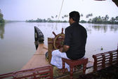 Man driving houseboat through backwaters, kerala, india — Stock Photo