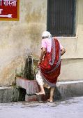 Old lady washing her feet, rishikesh, india — Stock Photo