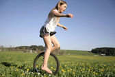 Young girl monocycling in field — Stock Photo