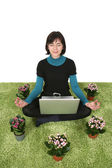 Woman sitting on grass with flowers around her meditating with a laptop — Stock Photo